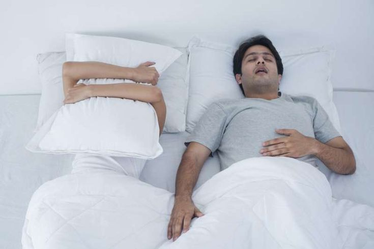 Drooling, Snoring, Talking, Walking: What Your Sleep Habits Reveal About Your Health - man snoring while partner has pillow over her face: Most snoring is harmless, but if it involves a pause in breathing followed by a gasp, it could be a sign of sleep apnea.