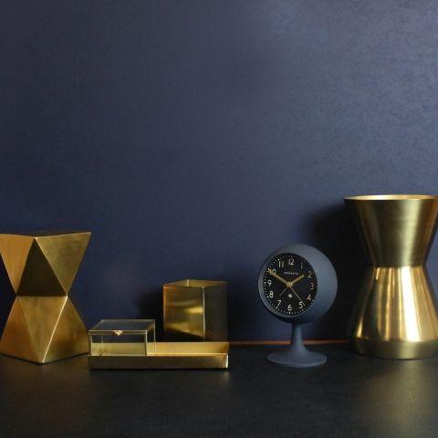 The Dome alarm clock by Newgate Clocks. A contemporary podium alarm clock in petrol blue.  Dark navy blue walls interior. Brass homeware and desk accessories.