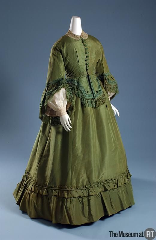 Afternoon dress - The second half of the 1860s saw the waning of the cage crinoline that had dominated fashion for almost a decade. The enormous, dome-shaped crinolines of the 1850s gradually flattened in front, shifting fullness to the rear of the skirt. In this particular example, the new silhouette is emphasized by the small train of the skirt and fringed peplum of the jacket-like bodice. Fashions of the 1860s were generally more assertive than those of the previous decade.