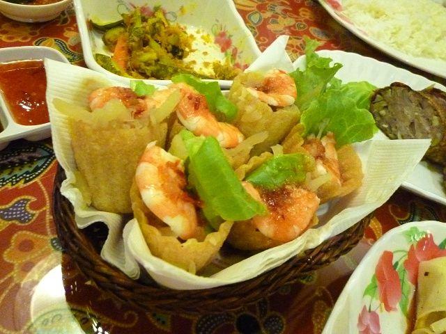 クエ・パイティー(Kueh Pie Tee) クエ・パイティーは別名「トップ・ハット(シルクハットの意)」とも言われる、可愛い前菜です。名前のとおり、帽子をさかさまにしたようなタルト風の小さなカップの中に、千切り大根の甘煮や小エビ、錦糸卵などが入っています。 エビの上にはチリサンバルがかけられており、ほんのり甘い具と、ピリ辛なチリとの絶妙なハーモニーを味わえます。サクサクしたタルトの器と中身の相性が良いうえに、見た目も華やかで写真映えは抜群。華やかな装飾を好んだ、ニョニャたちの感性が活かされた料理です。プラナカンはお正月にこの瀟洒な料理を食べていたそうです。今ではシンガポーリアンたちに、おかずのみならず手軽なおやつとしても親しまれています。