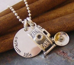 Such a fun necklace for anyone who loves to take pictures!    This necklace features a sterling circle that has been hand stamped with Capture Life!    It is paired with an adorable Sterling Silver Camera Charm.    It hangs on a sterling silver beaded chain