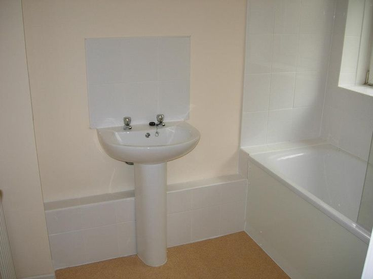The spacious bathroom is finished in simple white tiles. http://www.ppmsltd.co.uk
