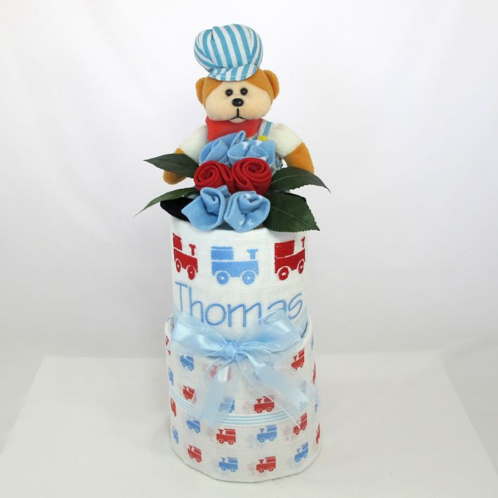 Personalised baby wrap nappy cake. Two cotton muslin baby wraps one personalised, baby socks and bib, a train driver teddy bear and filled witjh new born nappy's.