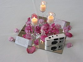 Inexpensive wedding centerpieces: The centerpiece above was created from a number of votive candle holders placed on a mirror tile. A little color is added by sprinkling rose petals on it.