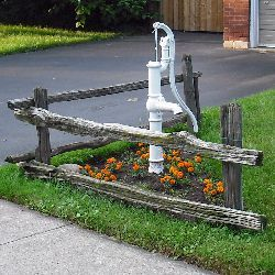 I like the triangular shaping of this split rail....not necessarily the flowers, or pump, but the shape...