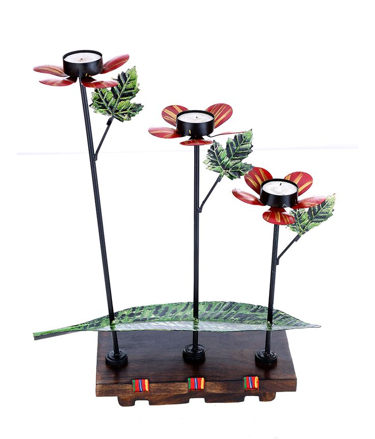 This beautifully crafted candle holder is in shape of three flower with leaves and stalk. The stalk are standing on a big metal leaf. A wooden platform which is again uniquely crafted supports them below and enhances the beauty of the flowers. These flowers are artistically designed and coloured and have a provision for a tea light holder in the middle
