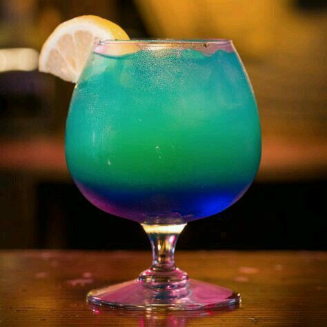 Sweet Poison-1 oz. Light Rum, 2 oz. Coconut Rum, 1 oz. Blue Curacao, Pineapple juice, Pineapple wedge (for garnish)