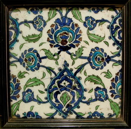 A DAMASCUS TILE . . . . . . . . . . . . . . . . . . . . . . . . . . . . . Syria, circa 1600 Stonepaste with underglaze polychrome decoration 26 x 26 cm the white ground of each with scrolling tendrils linking saz leaves around cusped blue and turquoise arabesque medallinos alternating with palmettes, details in manganese