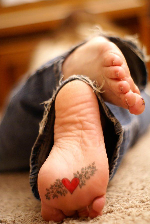 Heart under foot Tattoo - At the seat of the emotions, the red heart tattoo embellished with green leaves signifies joyful love of the young girl.