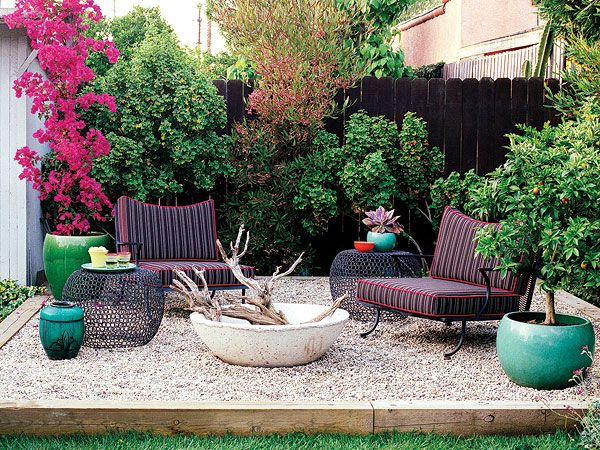 Vintage wrought-iron chairs, rusted metal side tables, and brown cushions make this space invitingly casual and play off the deep brown fence behind. A purple hop bush provides hits of red and orange. The 'den's' floor is covered with pea gravel, making this Los Angeles backyard perfect for parties. (Photo: Coral Von Zumwalt)