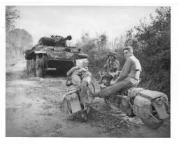 Panther (RD : 5/08/44) = [Deux motards, le soldat Raymond Bennett et le sergent Harvey Davis se reposent sur leur moto en compagnie d'un autre soldat américain (en arrière-plan, l'épave d'un panzer) ].