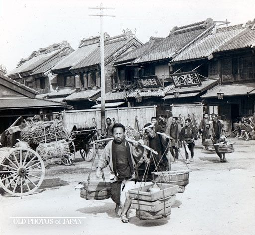 Men carry buckets with fish at the fish market in Nihonbashi,