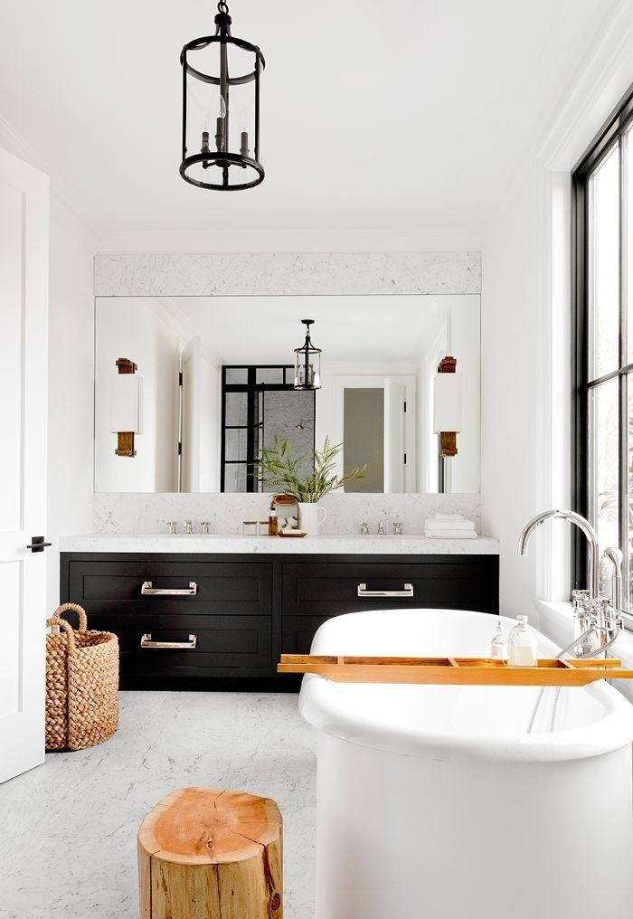 Beautiful black and white bathroom with iron lantern and freestanding bathtub.