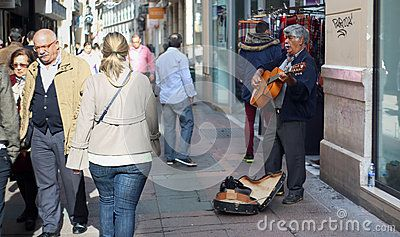 Street guitar player in old town Malaga. Tourists passing by.