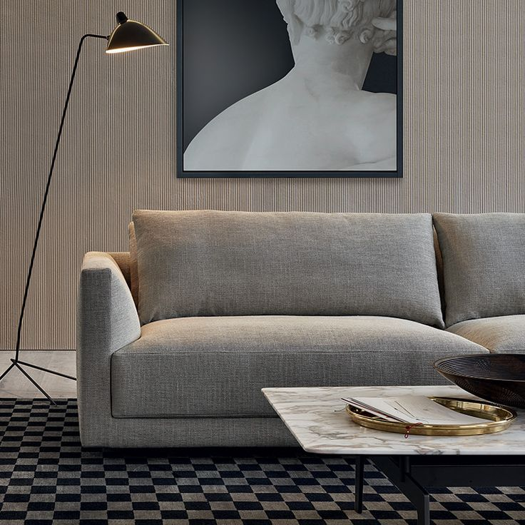 Poliform_Bristol modular sofa with removable fabric covering. Tribeca coffee table with bronze painted metal structure and top in calacatta oro marble.