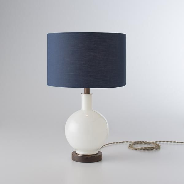 Perfect atop a nightstand or occasional table, the Bond lamp has a round, hand-blown glass base crafted from vintage molds. It supports a fabric drum shade and