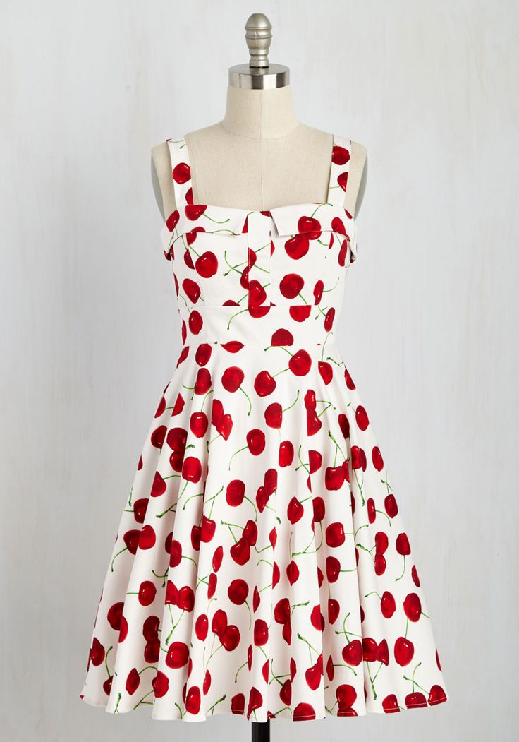 """Strutting stylishly past the cafe, you overhear onlookers rave about that """"rockabilly diva's beautiful white dress!"""" With a collared-and-padded bust, one-inch straps, and a swingy, A-line cut that's patterned with red cherries, your cool back-tied frock steals the subject of conversation."""