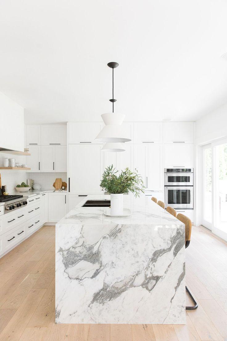 Leichte, natürliche, moderne weiße Küche mit Lederhockern und einer dicken Marm …