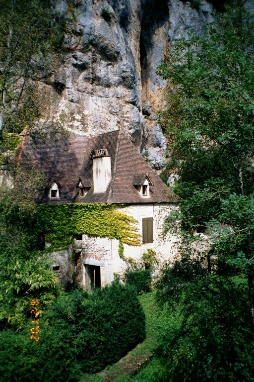 A house along the River Célé built into the side of a cliff, near Sauliac-sur-Célé, Midi-Pyrénées, France