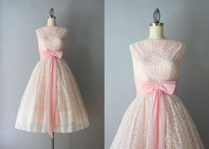 Zeer vroege jaren 1960 partij jurk in wit kant over bleke roze taffeta. De jurk heeft een bateau-hals en een ingerichte bovenlijfje met een verzamelde tailleband van pure, roze, chiffon die is overgoten met een grote boog. De rok is vier volledige lagen: de witte lace overlay, een tussenlaag van tulle, de roze taffeta voering en een ingebouwde, gesteven gaas petticoat. De jurk sluit met een terug metalen rits.  ◊ voorwaarde: uitstekend! Mooie vorm, schoon en klaar om te dragen. ◊ label: geen…