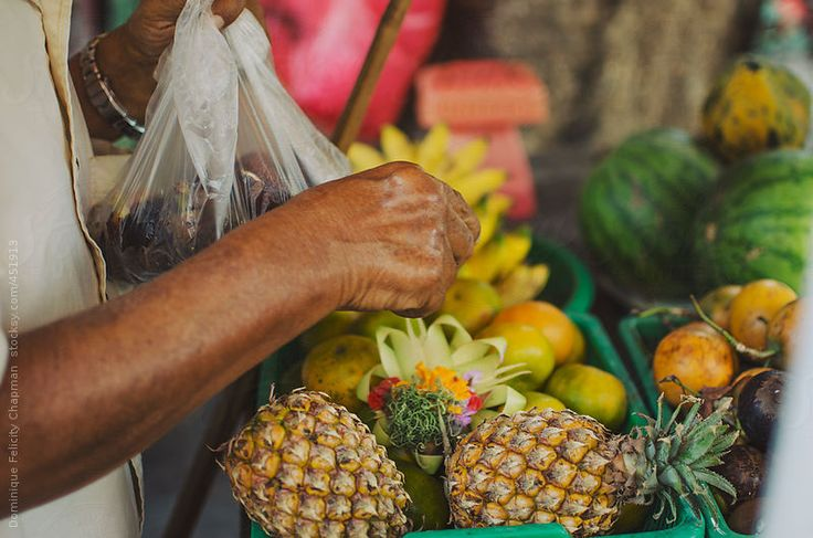Man packing fruit into bag from street stall by DominiqueFelicityPhotography | Stocksy United