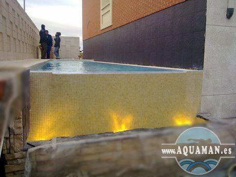 Piscina con rebosadero en un lateral y recojida de aguas en canaleta.