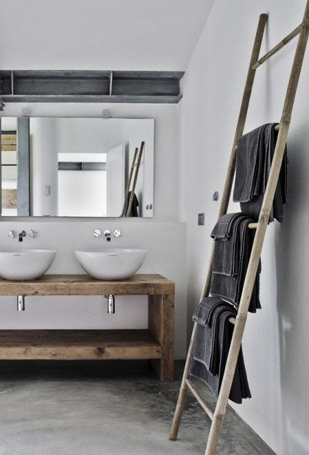 Scandinavian bathroom featuring concrete floors, a wooden vanity, twin sinks and a leaning wooden ladder for towels | Planete Deco
