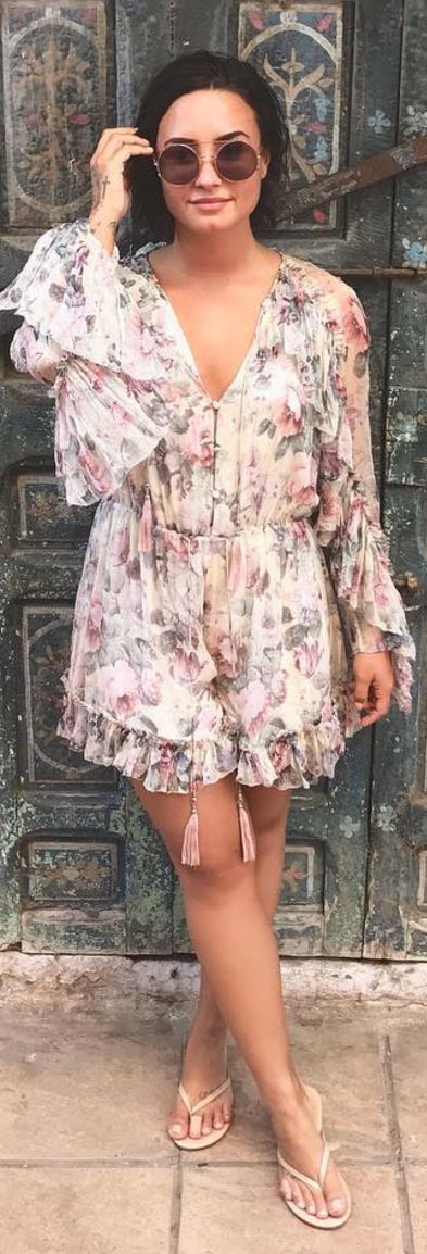 Who made  Demi Lovato's nude flip flops, round sunglasses, and rose print ruffle romper?
