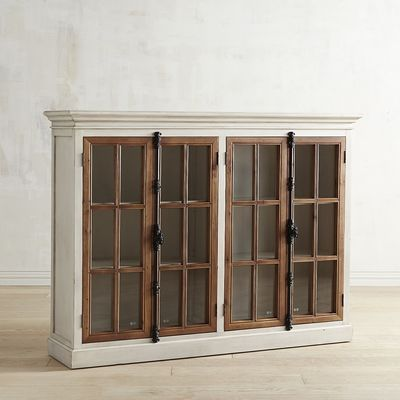"""Originating in 19th century Europe, the """"Cremone bolt"""" is a traditional casement-window locking device with a latch/handle mechanism. Featured on all our hand-hewn Cremone cabinetry, it's as beautiful as it is functional. Also featured: Antique white wood frames with protracted crown molding, contrasting natural wood casements and tempered pane-glass windows. Our 4-door low cabinet houses two adjustable shelves."""
