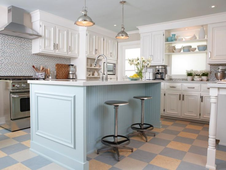 Always one to mix styles and materials in the kitchen, designer Sarah Richardson mixed colors here as well, choosing to paint the wall and base cabinets white then making the island a focal point with cheery robin's egg blue. The ceiling, painted a lighter shade of blue, ties in the island while making the white cabinets really pop.