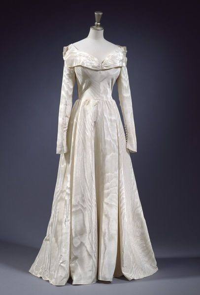 Wedding dress in cream silk moiré with a full length, full skirt, closely fitted bodice and long tight sleeves. The neckline cut wide and lo...