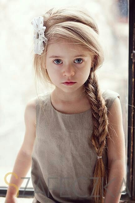 Beautiful little girl with a long blonde braid and a white flower in her hair