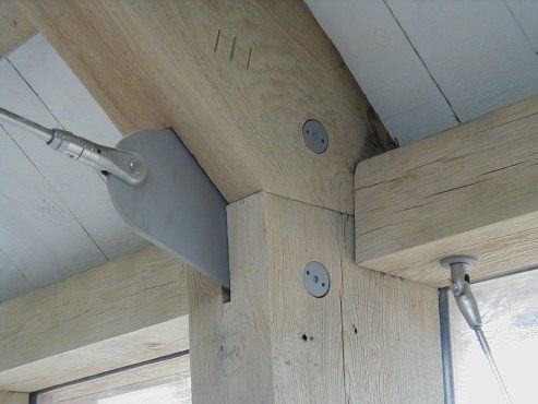 Mixture of contemporary bead-blasted stainless steel fixings and heavy green oak framing on Cliff-side house in Devon
