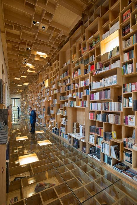 Mexican firm Taller 6A has renovated a library inside an eighteenth-century building in Mexico City, adding a bookshop with hundreds of wooden boxes on its walls, its ceilings, and under its glass floor