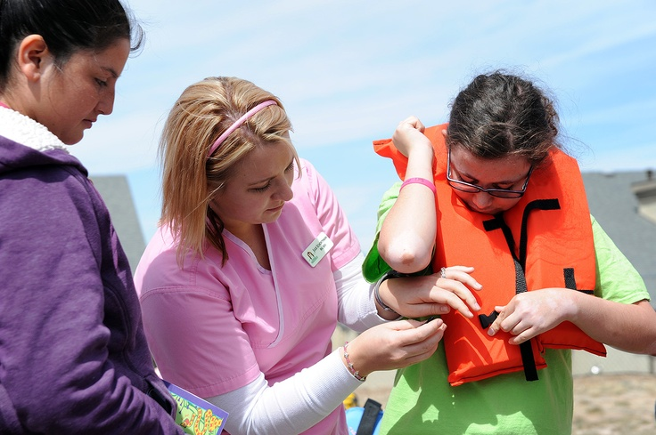 School nurse Julie Schortmann explains fitting and fastening life jackets for 12th grader Breazyihannah Ross, 19, during safety activities April 25 at Springs Ranch Elementary School in Falcon School District 49. Ross was visiting with other students in the Mild/Moderate Needs Program at Falcon High School. The educational activities were delivered by the Junglemobile from Children's Hospital Colorado in Denver.