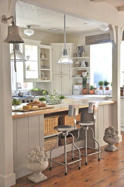 Vintage but modern farmhouse kitchen. Love everything, the floors, stools, basket storage, lights, corner cabinet, cornices and the bell!