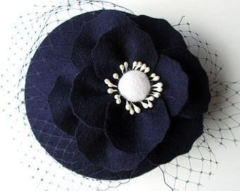 A gorgeous poppy bloom nestles on a bed of veiling to create an elegant yet eye-catching cocktail hat. The hat is handmade from 100% wool felt in a vibrant red shade with black contrast centre (for difference colour options please contact me or leave a note at checkout).  Finish: Your hat is customised with your preference of fastening - elastic or headband. The elastic sits around the back of your head and can be hidden by your hair. If you have fine hair you may prefer a headband, in which…