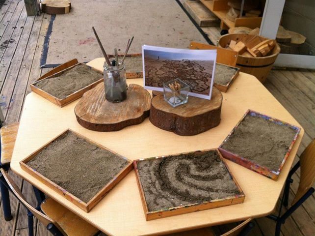 painting with sand/water..provocation in the middle. I also like the small tree stumps in the center as the holder