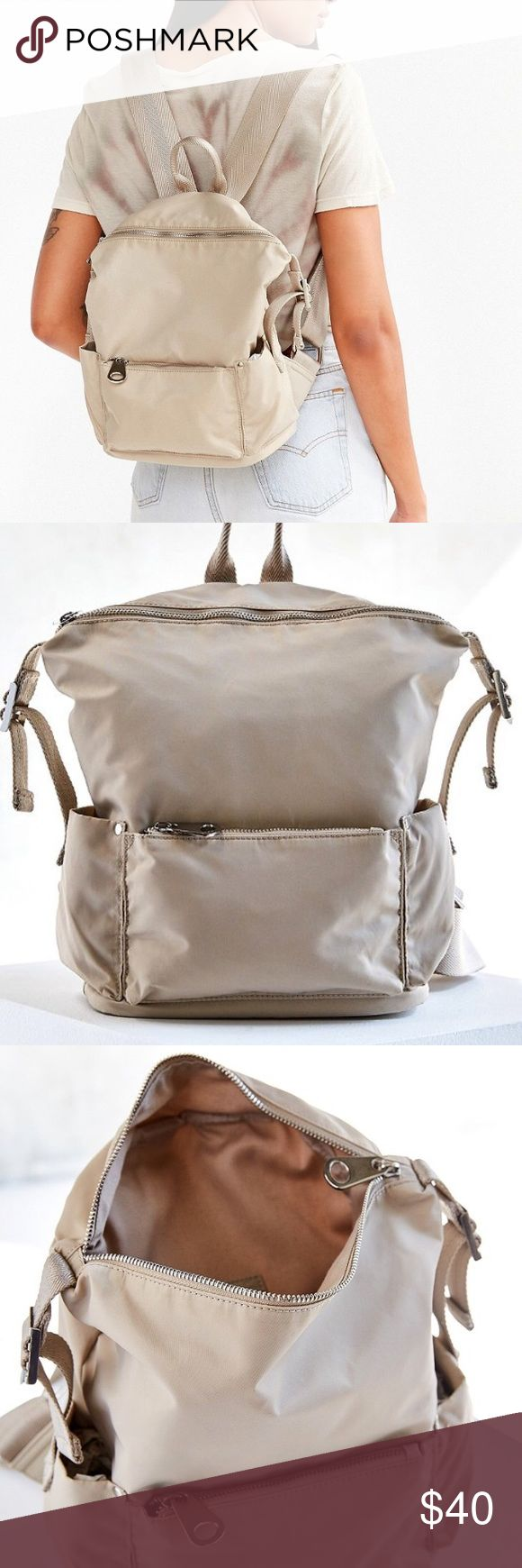 """Last OneNWT Urban Outfitters cream backpack Sporty-sleek backpack from the innovators at Silence + Noise, cut mini so you never over pack. Featuring exposed metal zipper closures at main compartment + front pocket with pouches at sides. Accented with adjustable woven buckles + shoulder straps cut wide complete with a top carrying handle. Perfect for concerts, brunch and everything in between. - Polyester.   Spot clean Length: 9.5""""Width: 5.25"""" Height: 11.5""""       Handle drop: 3.5"""" Urban…"""