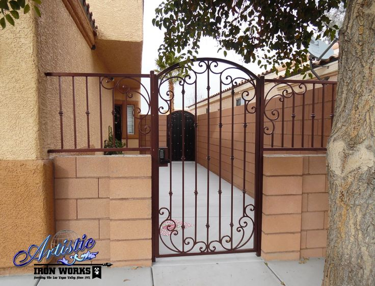 Wrought iron courtyard gate with scrolls and knuckles