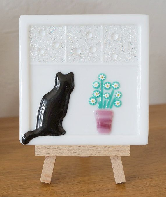 This is a beautiful small fused Glass Picture on a Wooden Easel of a black Cat sitting on a Window handmade by my Husband Mark John by layering different coloured Glass and Dichroic Frit and being fired in a digitally controlled Kiln by 1380Degrees.  Size of Fused Glass Picture : approx. 10cm x 10cm  Thanks for looking Doris