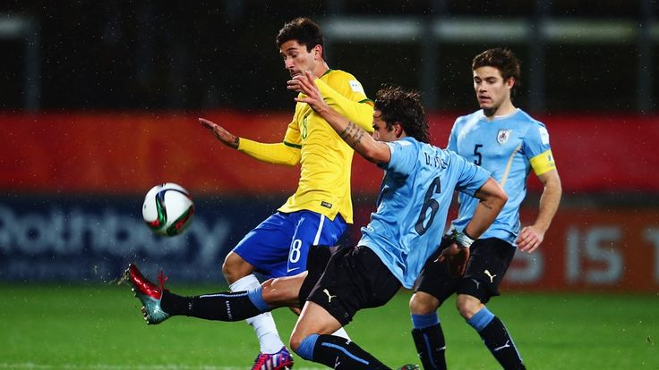 Boschilia of Brazil is challenged by Diego Poyet of Uruguay