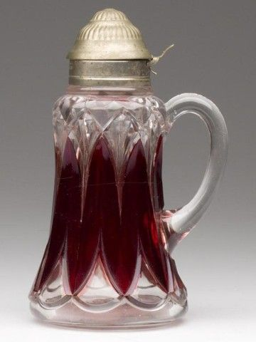 "HEAVY GOTHIC / WHITTON - RUBY STAINED SYRUP PITCHER, colorless, period lid with patent date. Columbia Glass Co./United States Glass Co. Late 19th/early 20th century. 7"" h overall. <BR><I>Undamaged.</I><BR> Provenance: Collection of Charles and Mitty Courtoy"
