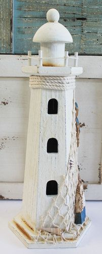 """White nautical wood lighthouse with fishnet, shells, and blue and white buoys stands approximately 13.5"""" high and is a great accent for any coastal themed room."""