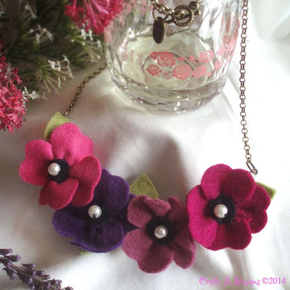 A beautiful, handmade felt flower necklace in gorgeous shades of pink and purple. The four stunning flowers are hung from an antique gold