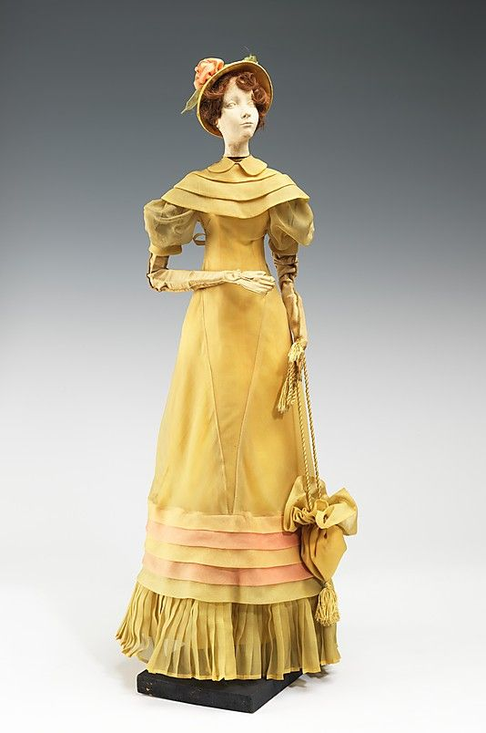 """""""1811 Doll""""  House of Paquin (French, 1891–1956)  Designer: Elegances Designer: Richomme Date: 1949 Culture: French Medium: metal, plaster, hair, silk, leather Dimensions: 30 1/2 x 10 1/2 in. (77.5 x 26.7 cm) Credit Line: Brooklyn Museum Costume Collection at The Metropolitan Museum of Art, Gift of the Brooklyn Museum, 2009; Gift of Syndicat de la Couture de Paris, 1949"""