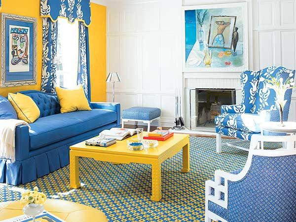 A wall covered in sunshine yellow suede forms a bold backdrop for the living  room's royal blue upholstery scheme. A yellow lacquered coffee table a