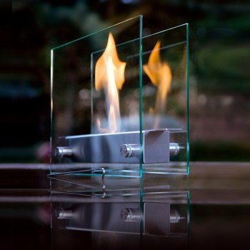 Stainless Steel and Glass Fireplace. Made from high-grade stainless steel and glass, this fireplace is a striking centerpiece for a low table or foyer. Doors open and close to adjust the flame size—and it will burn for 3-4 hours. Award-winning design for Carl Mertens by Wolf Wagner. $1,250.00