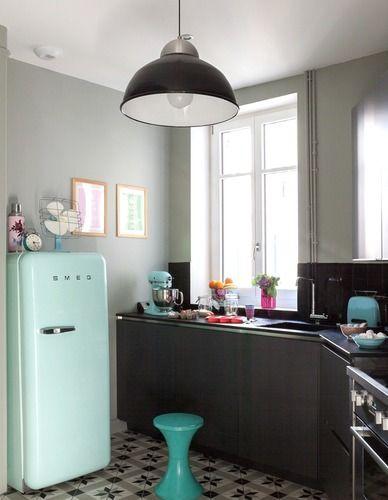 Une petite cuisine en coin aménagée avec des carreaux de ciment et des meubles en bois sombre.