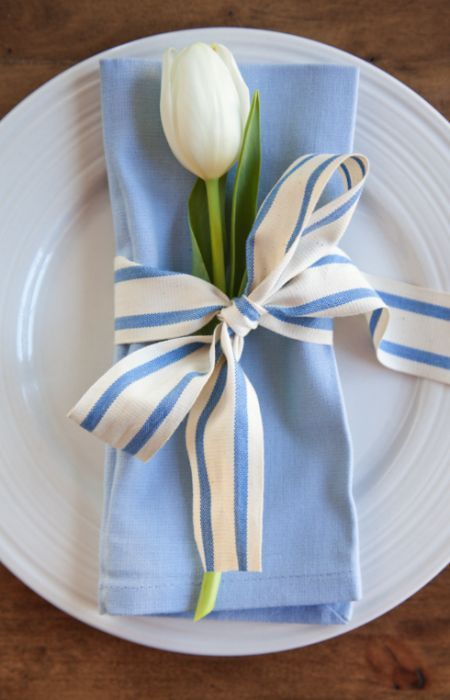 A white tulip and coordinating ribbon are all you need for a spring table setting.